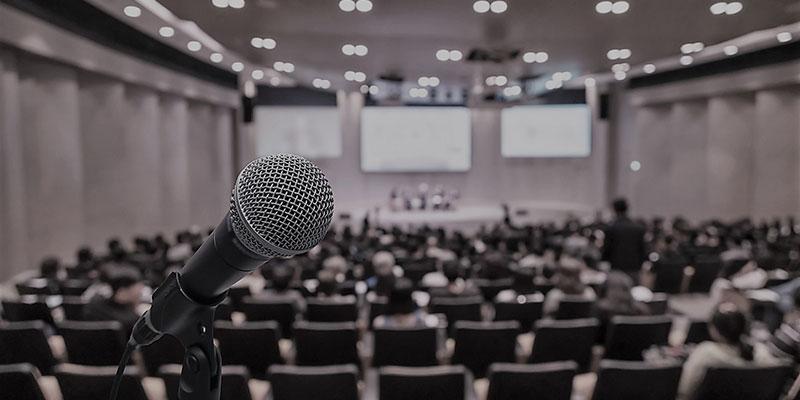 Salle de conférence et micro au premier plan